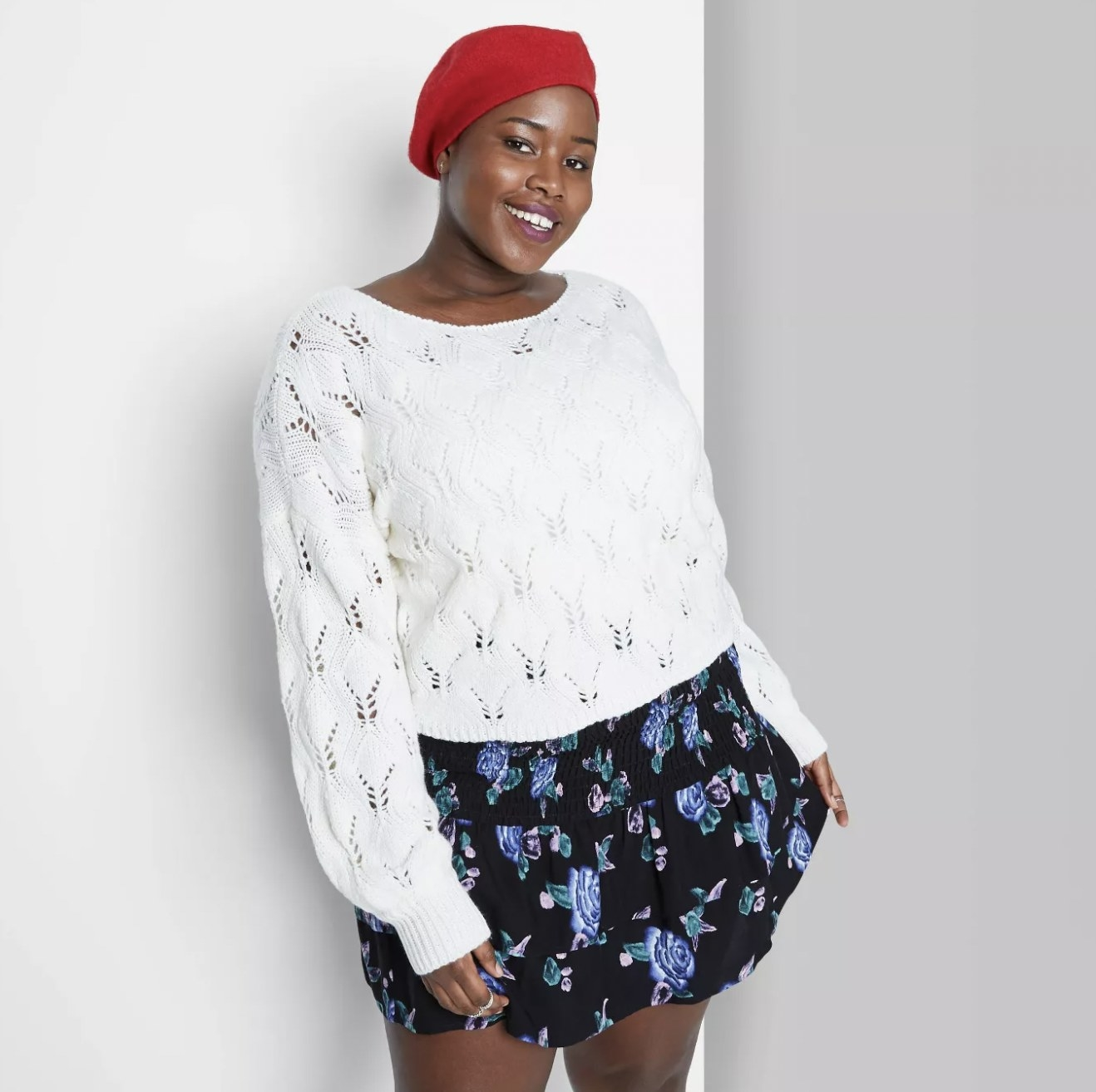 A model wearing a red hat, a white sweater, and a black skirt with purple flowers