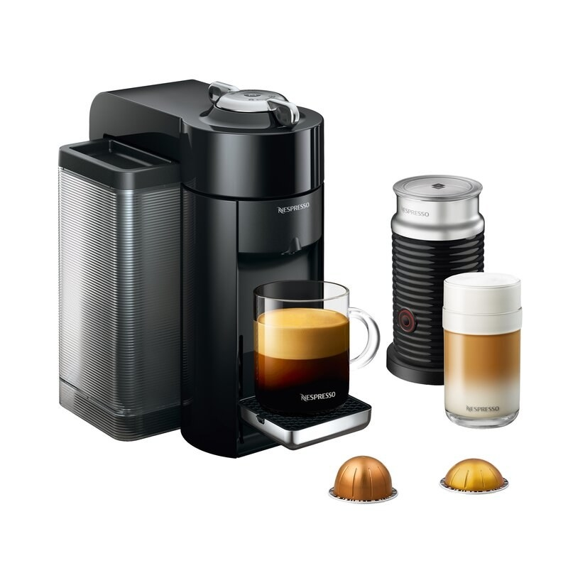 a nespresso espresso machine with a cup of espresso resting on it, with a milk frother next to the machine, a latte next to the machine, and two espresso pod inserts next to the machine