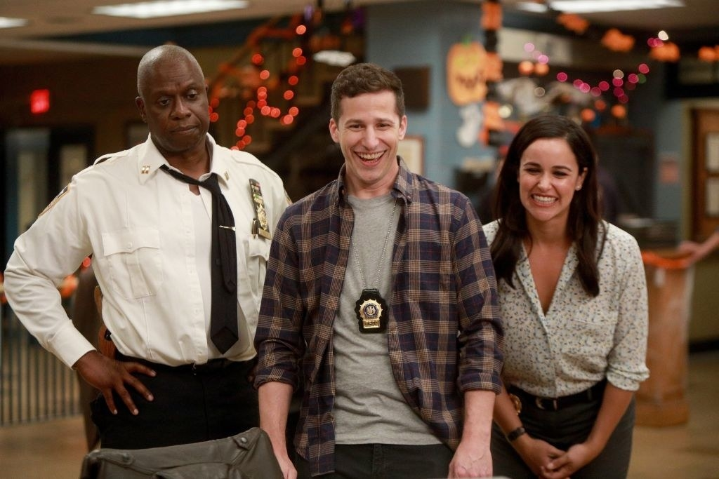 From left to right, Andre Braugher, Andy Samberg and Melissa Fumero standing next to each other as Andy and Melissa smile