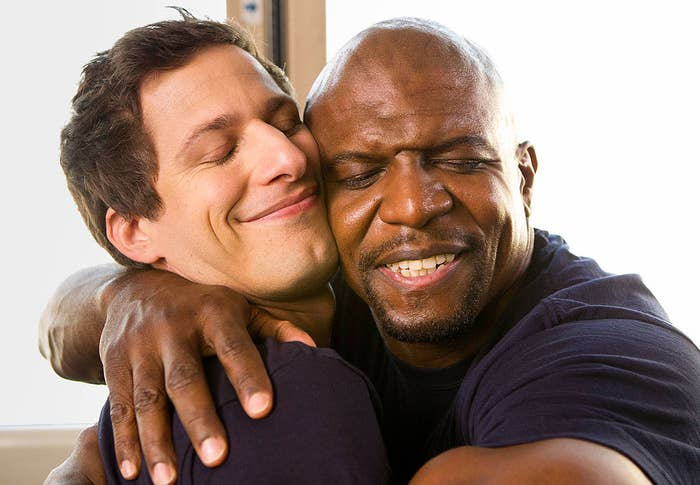 Andy Samberg and Terry Crews hugging in a scene from in BROOKLYN NINE-NINE