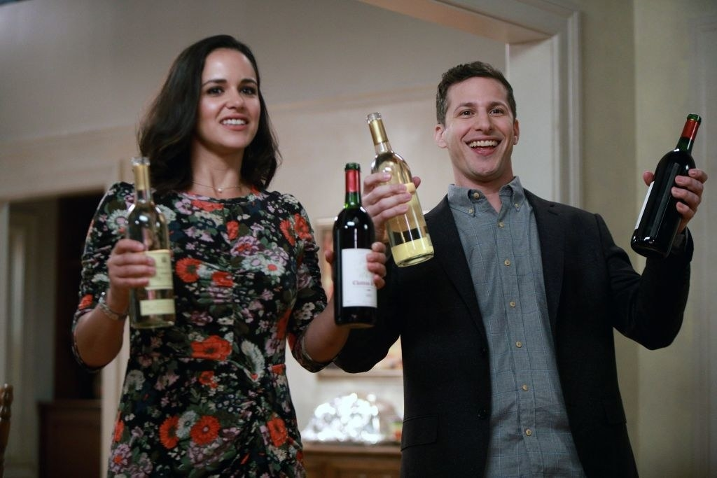 Melissa Fumero and Andy Samberg holding up bottles of wine in a scene from BROOKLYN NINE-NINE