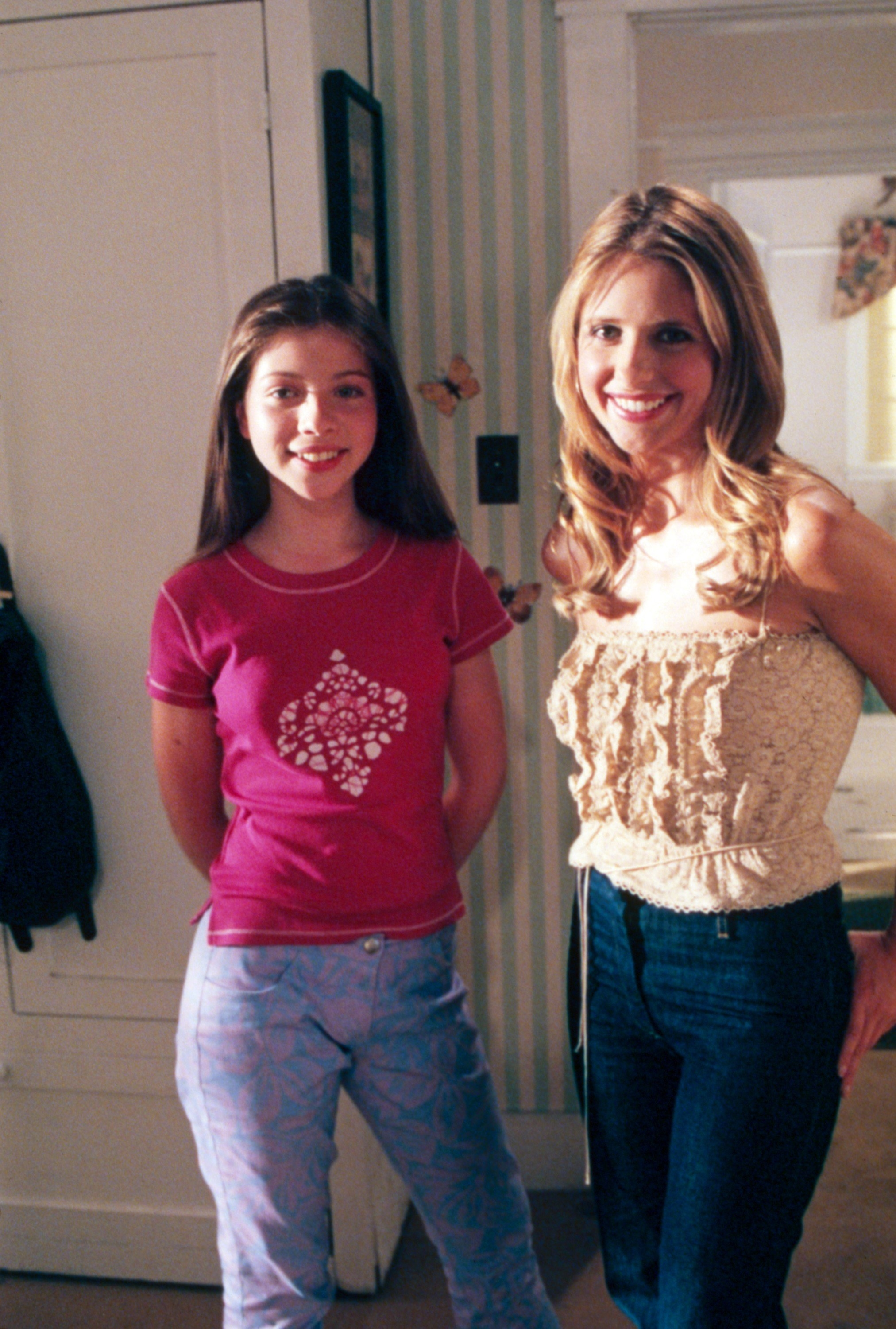 Michelle Trachtenberg and Sarah Michelle Geller stand next to each other on the set of Buffy the Vampire Slayer