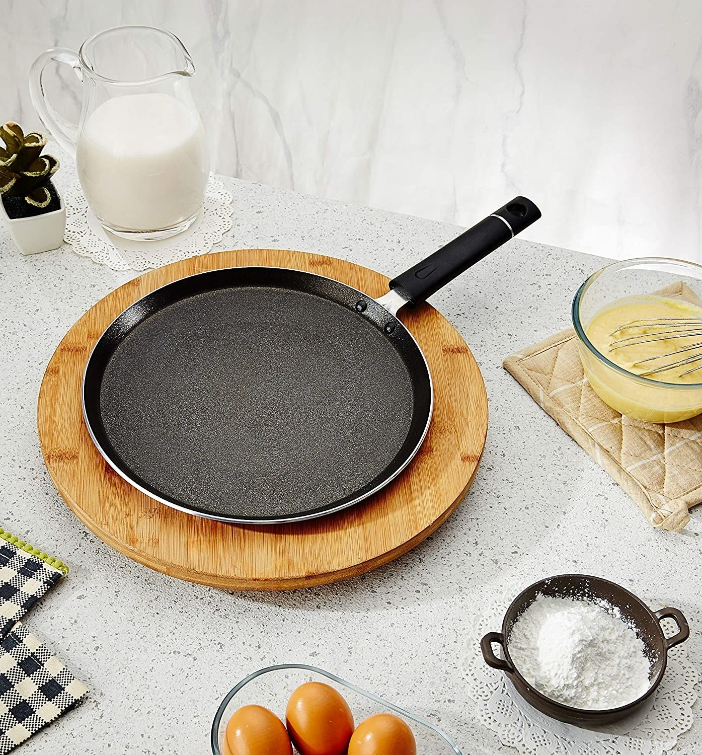 A non-stick tawa with eggs and flour