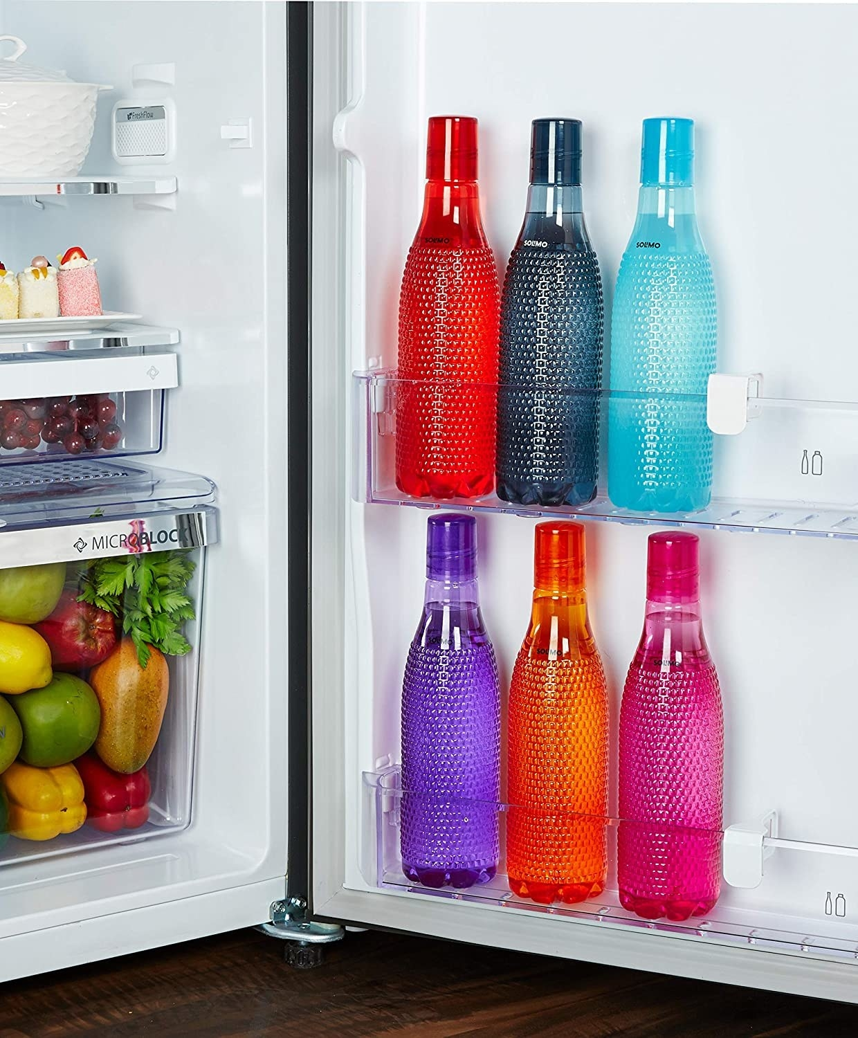 A set of colourful water bottles in a fridge