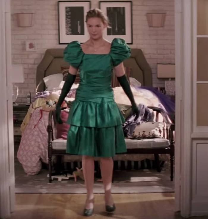 Jane wears a green 80s style dress with sad gloves
