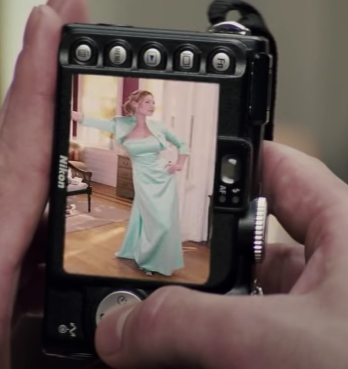 A shot of a digital camera with a picture of Jane on the screen wearing a long strapless mint green dress with a matching bolero