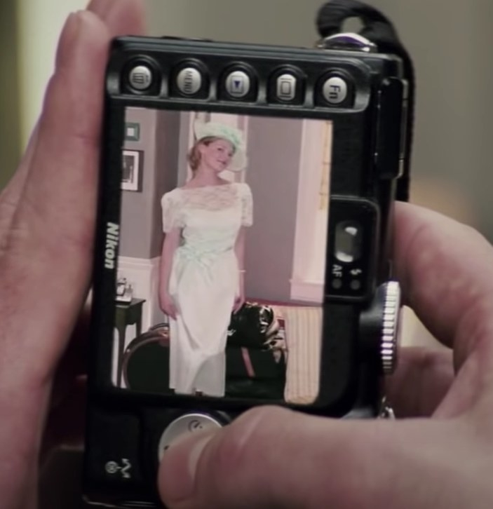 A shot of a digital camera with a picture of Jane on the screen wearing awhite dress with a lacy top half and a mint green ribbon and matching hat