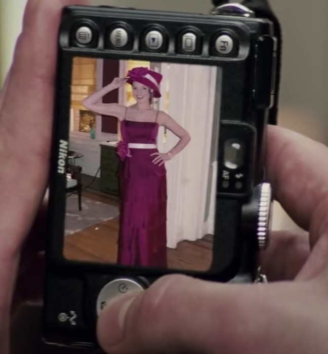 A shot of a digital camera with a picture of Jane wearing a long spaghetti strap dress and a matching hat