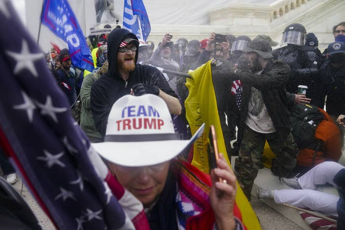 """Police and rioters outside the Capitol clash; in the foreground, a person wears a cowboy hat that reads """"team Trump"""""""