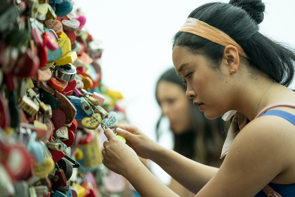 Lara Jean staring at a locket surrounded by hundreds of lockets on a fence