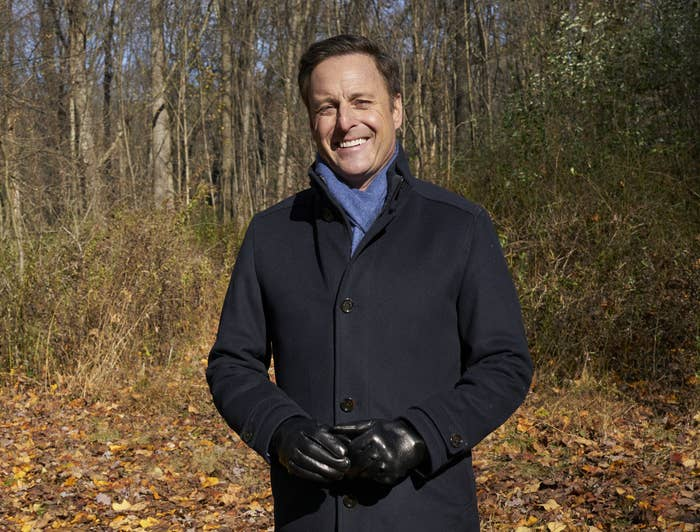 Chris Harrison standing in the woods wearing a winter coat, blue scarf, leather gloves