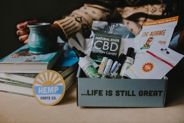 a person holding a mug next to a Hemp Crate packed with CBD cotton candy, CBD lip balms, vegan snacks, and other products