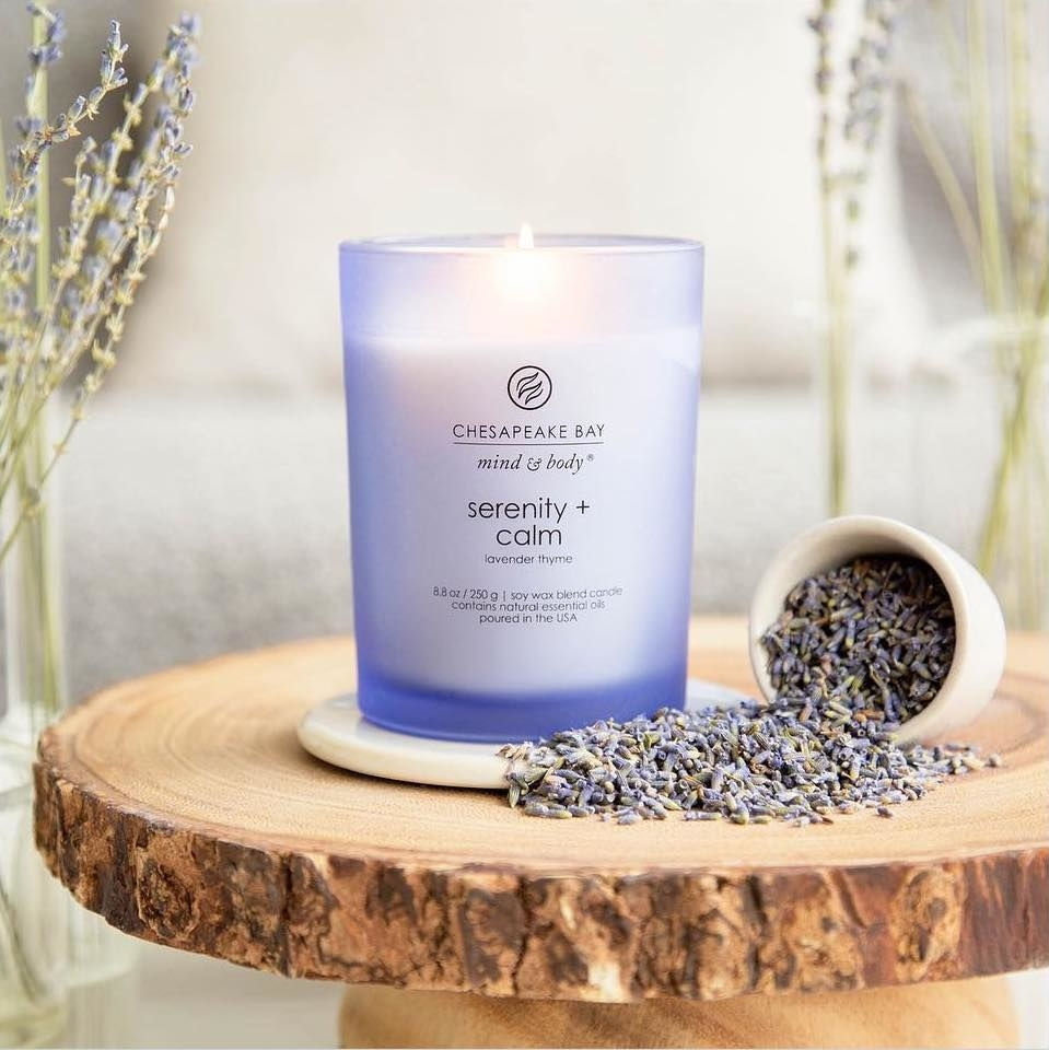 the serenity and calm candle on a wooden table with a jar of dried lavender next to it
