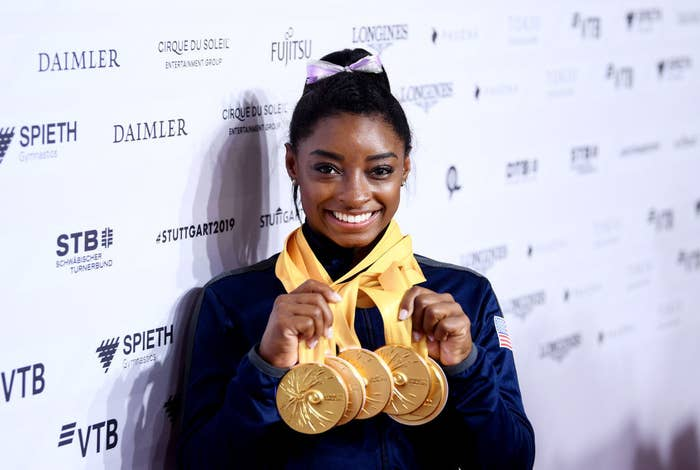 Simone Biles posing with her Olympic gold medals around her neck