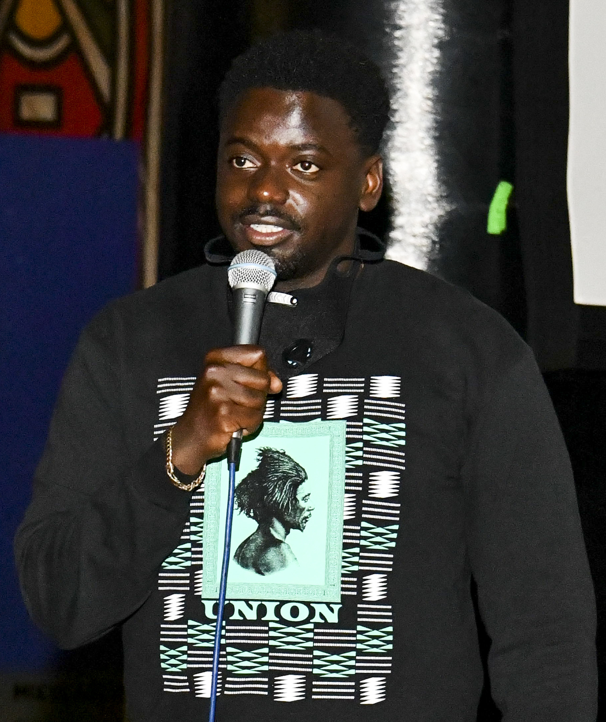 Daniel speaking into a microphone while wearing a hoodie with the image of a Black man with the word 'Union' on it