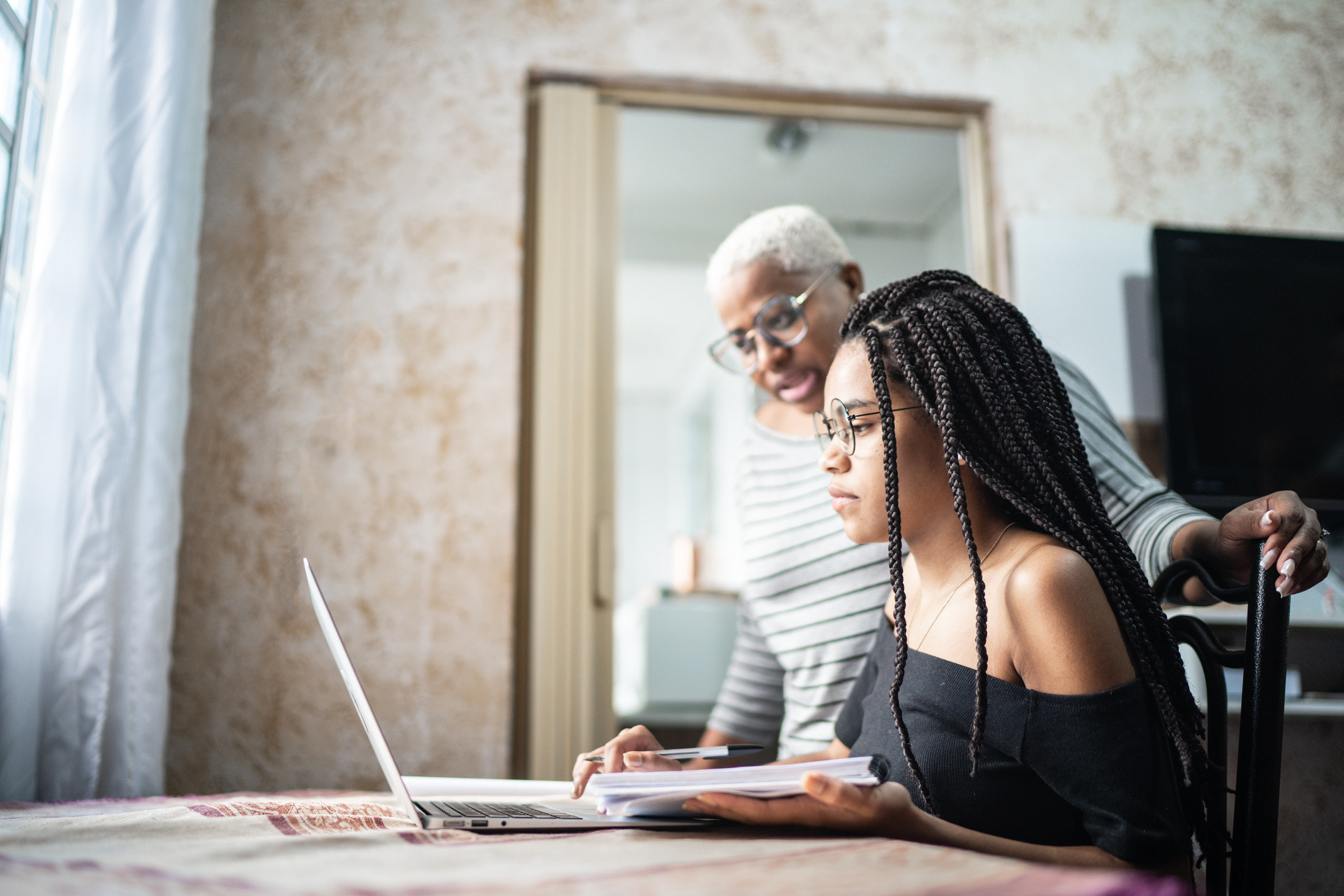 A young Black woman with braids and eyeglasses looks at a laptop and as an older Black woman looks over her shoulder