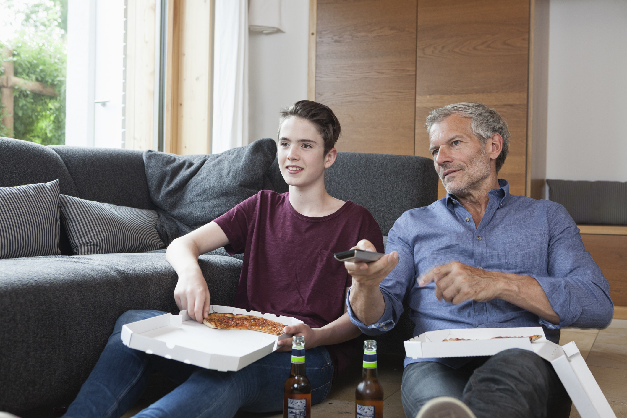 A young white man and an older white man eating pizza and watching tv as they sit on the floor