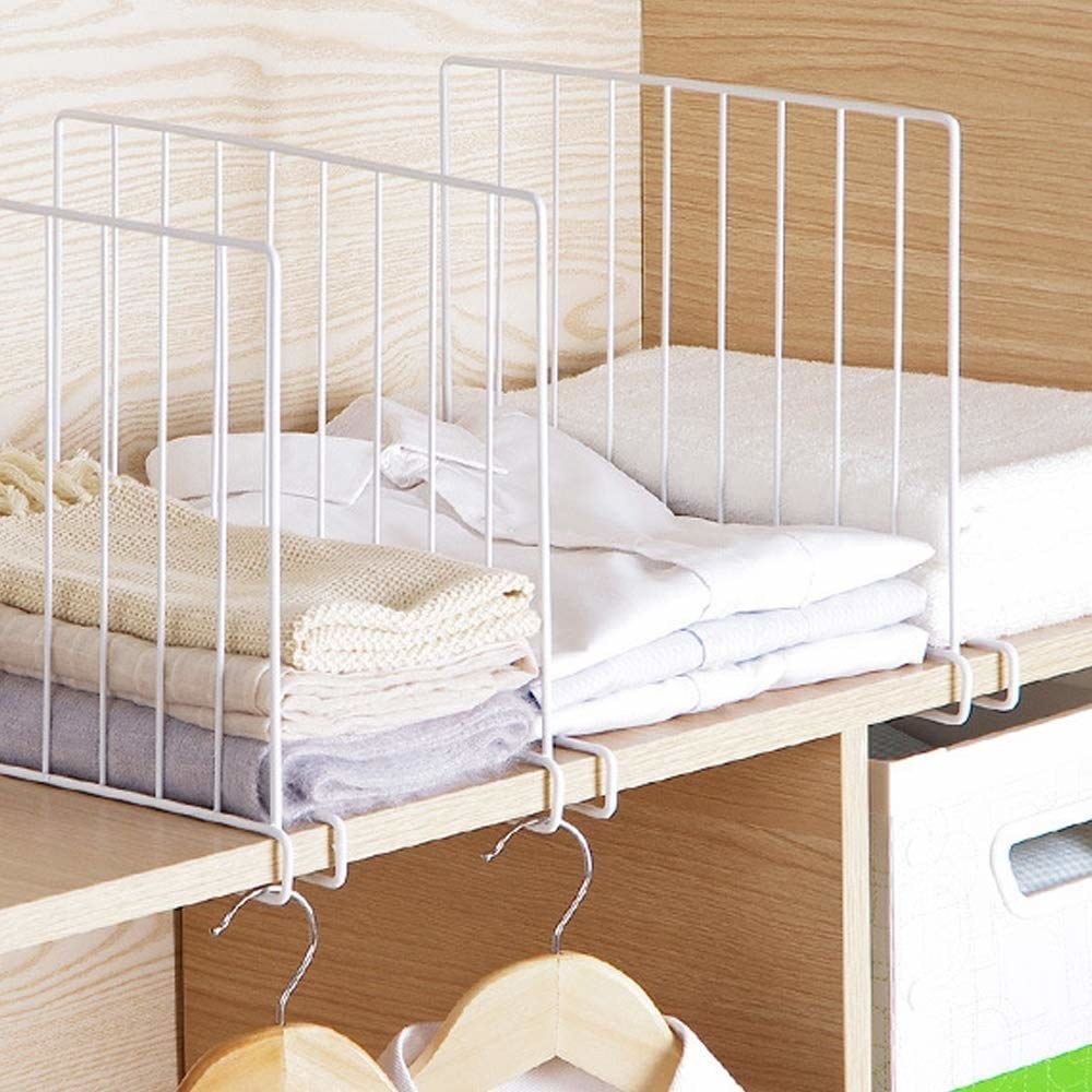 Shelf dividers with clothes between them.