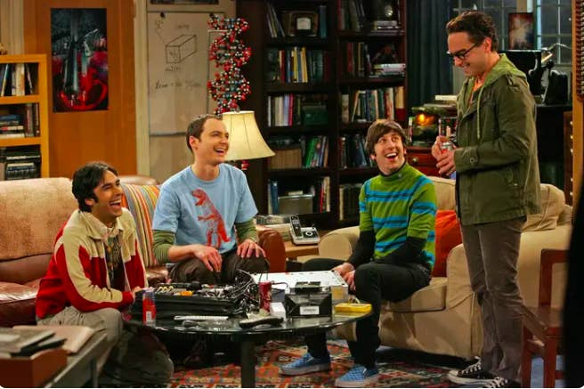 Big Bang Theory characters Koothrappali, Sheldon, Wolowitz, and Leonard sitting together and laughing