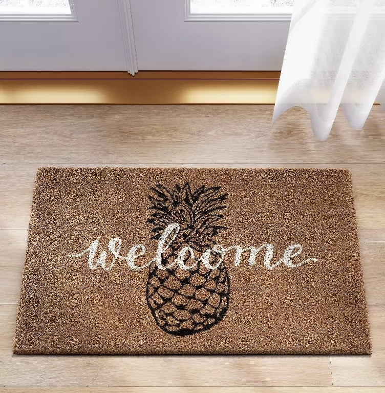 A doormat with a pineapple graphic and welcome written across it