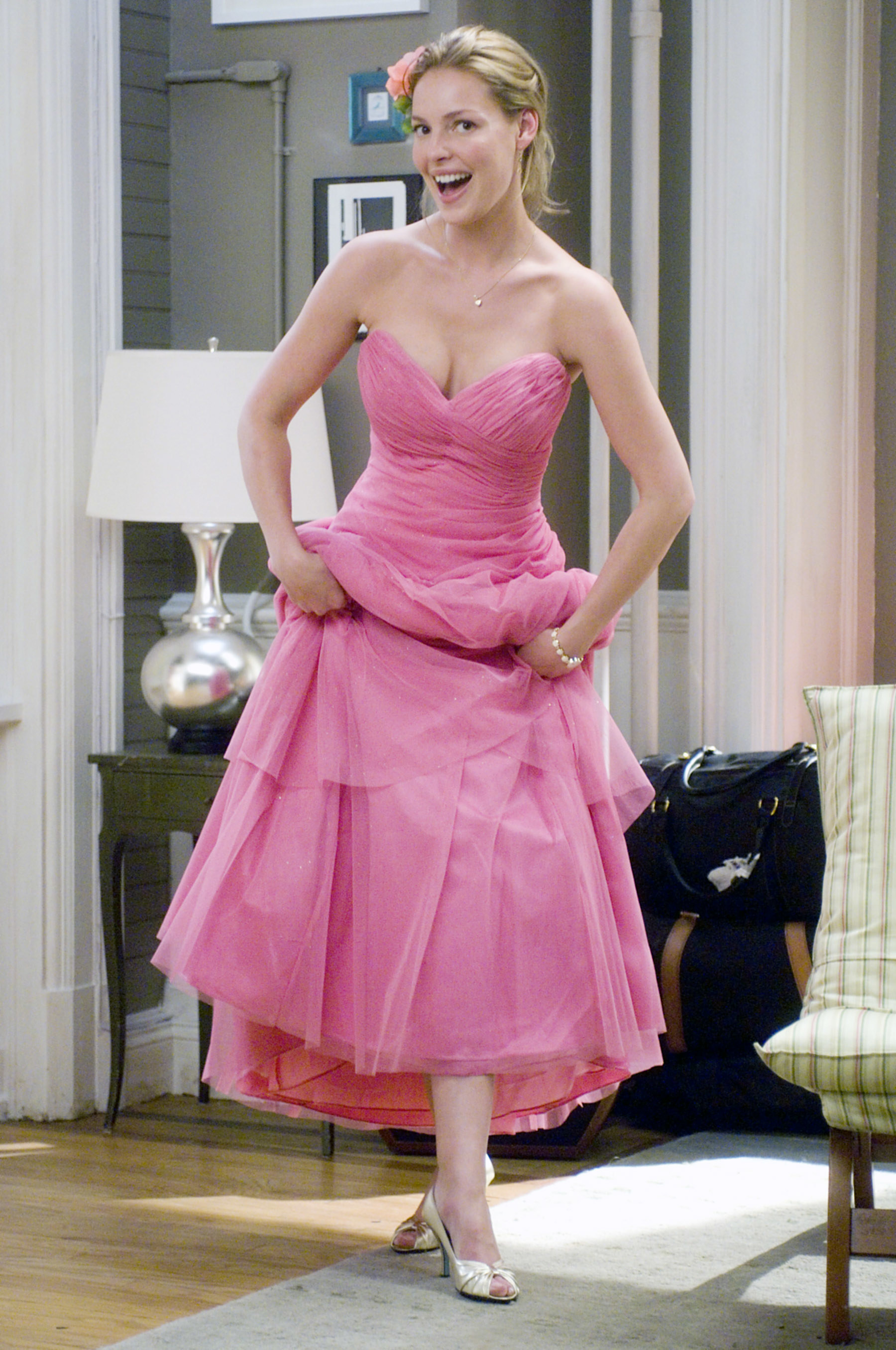 Jane lifts up the hem of a pink dress with a sweetheart neckline