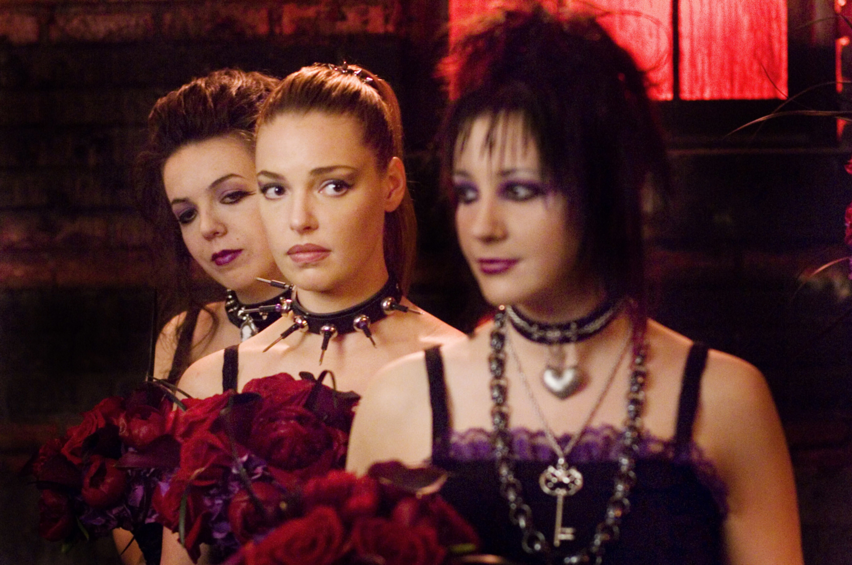 Jane stands between two women wearing a spiky choker and holding flowers