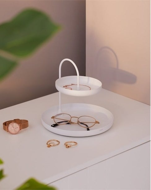 A two-tiered tray with jewelry and glasses on it