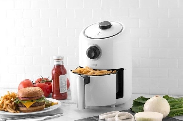 The air fryer with fries in it next to a burger on a plate