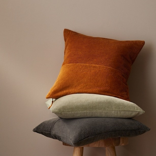 Three corduroy pillows stacked on a stool