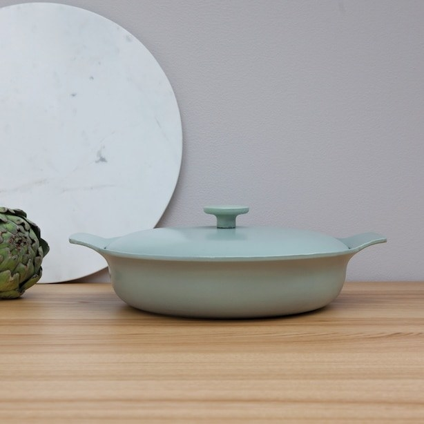 An enamel cast iron skillet on a counter top