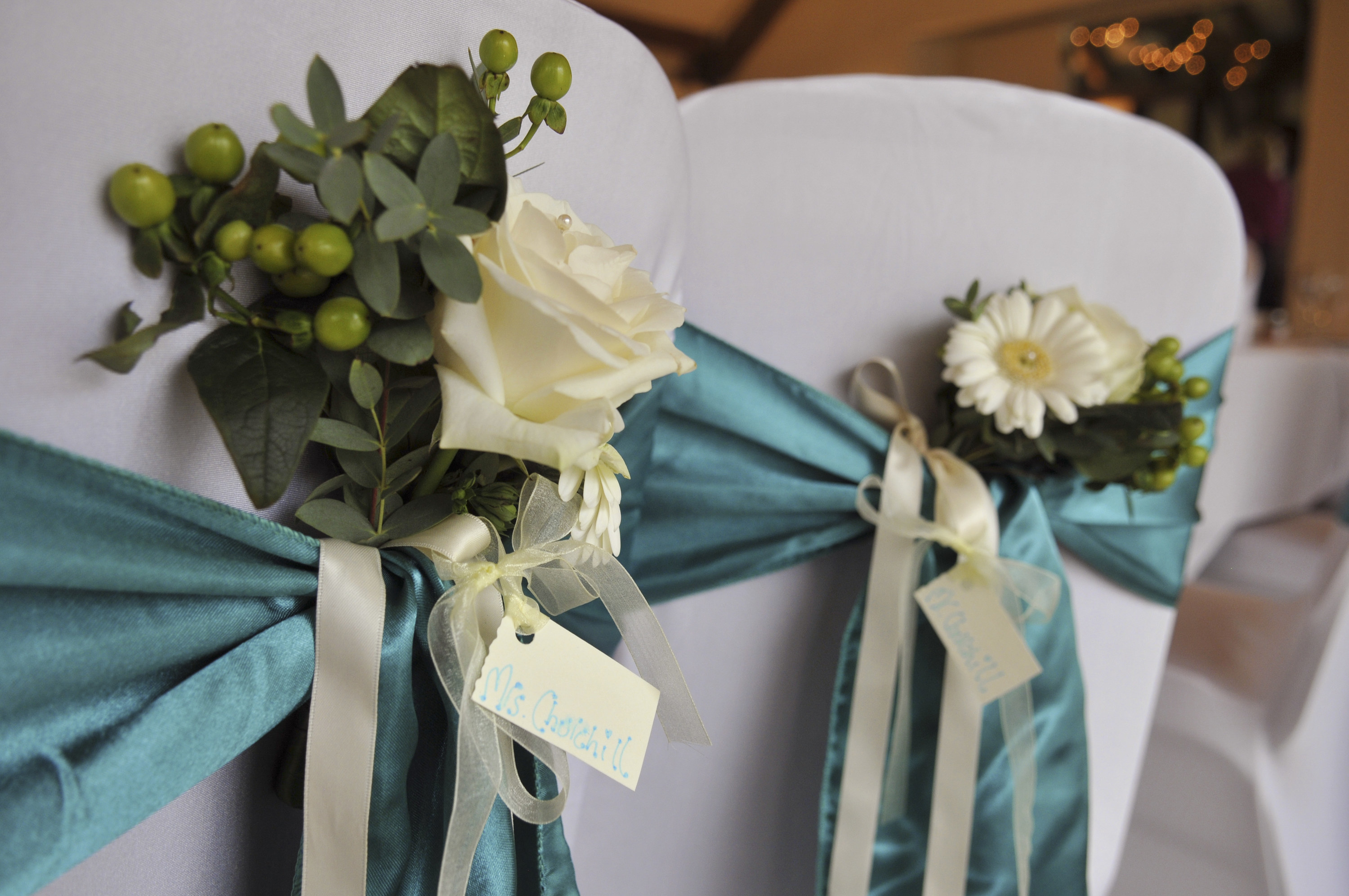 White chair covers with blue ribbon and flowers