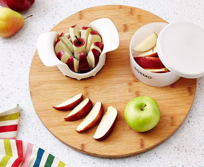 An apple cutter with sliced apples in a storage box next to it