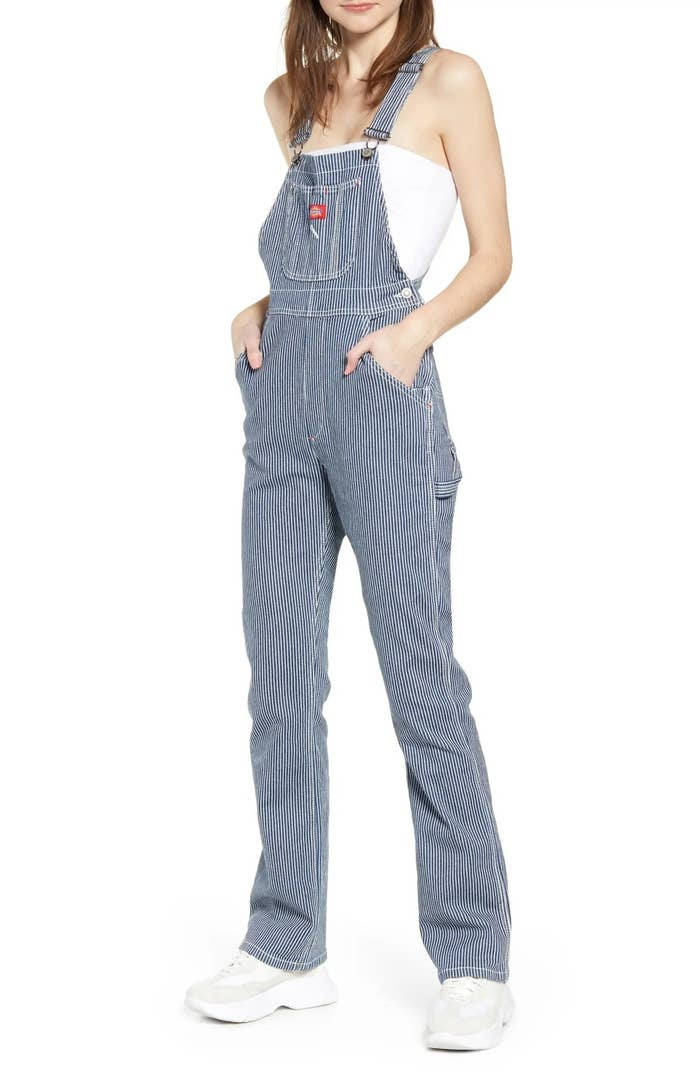 A model wearing the overalls, hands tucked in pockets