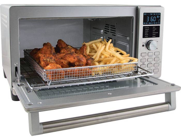 The oven with chicken and fries inside