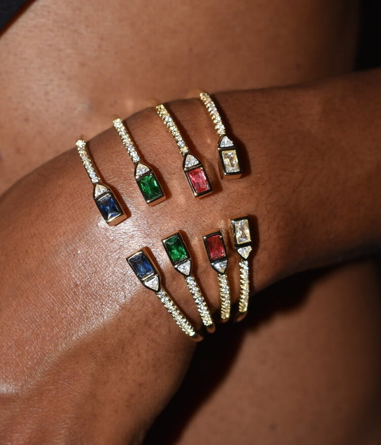 model wearing four open bangles with blue, red, green, and clear stones
