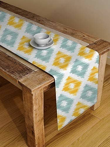 A yellow and blue ikat table runner spread out on a wooden table.