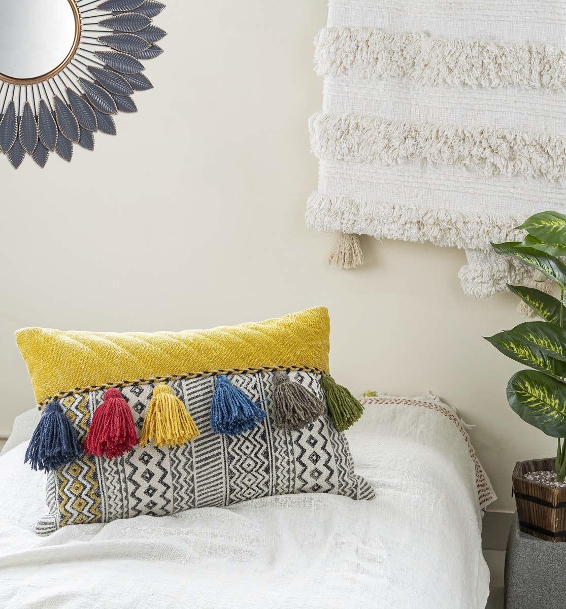 A tasseled Jaipuri hand-block cushion in white and yellow.