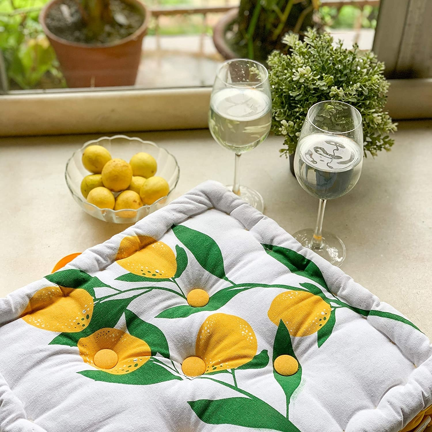 A square floor cushion with a lemons printed on it. It's kept next to a bowl of lemons and two wineglasses.