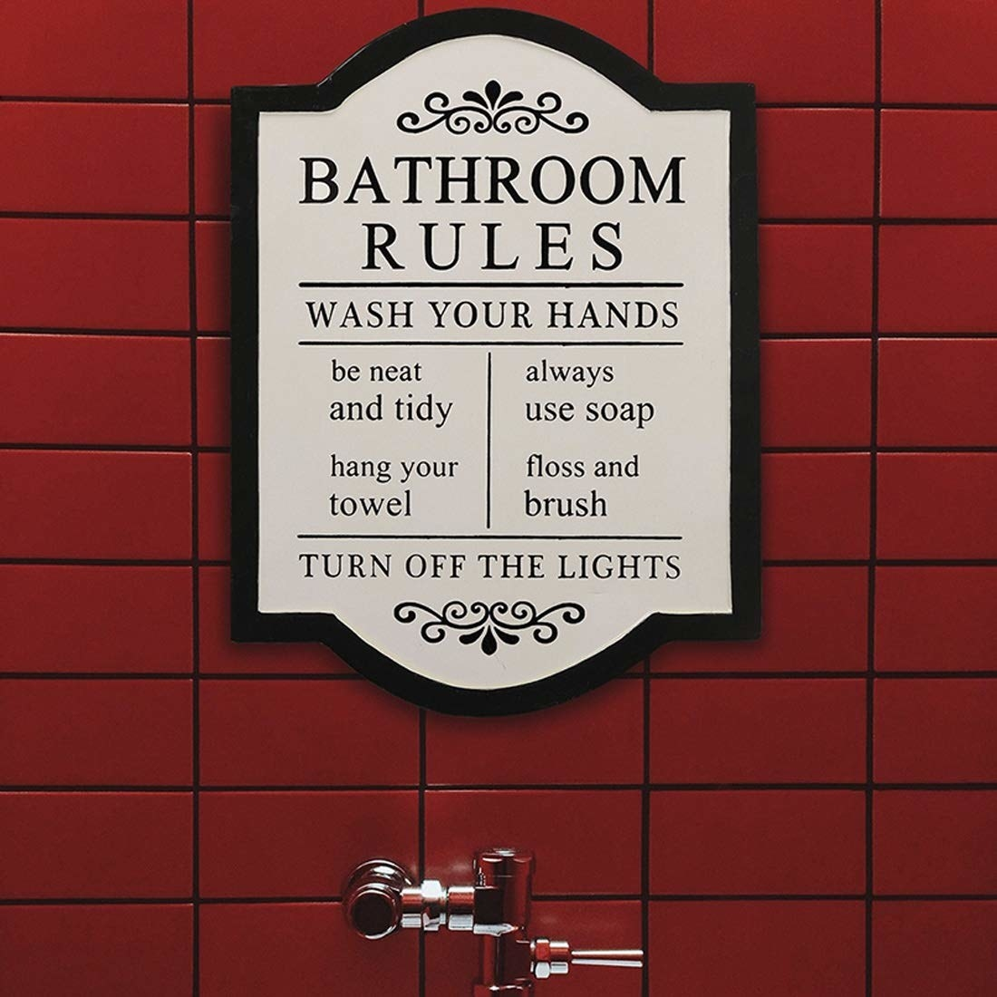 """A frame with bathroom rules like, """"Be neat and tidy"""" and """"Hang your towel"""" printed on it."""