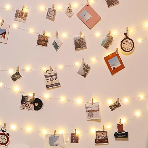 The string lights being used to display photos and other prints