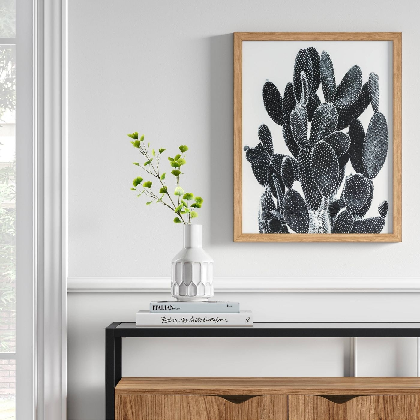 black and white catcus print hanging up above a console table