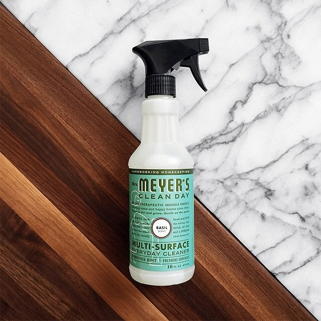 A flatlay of the multi surface cleaner on a wooden and marble surface
