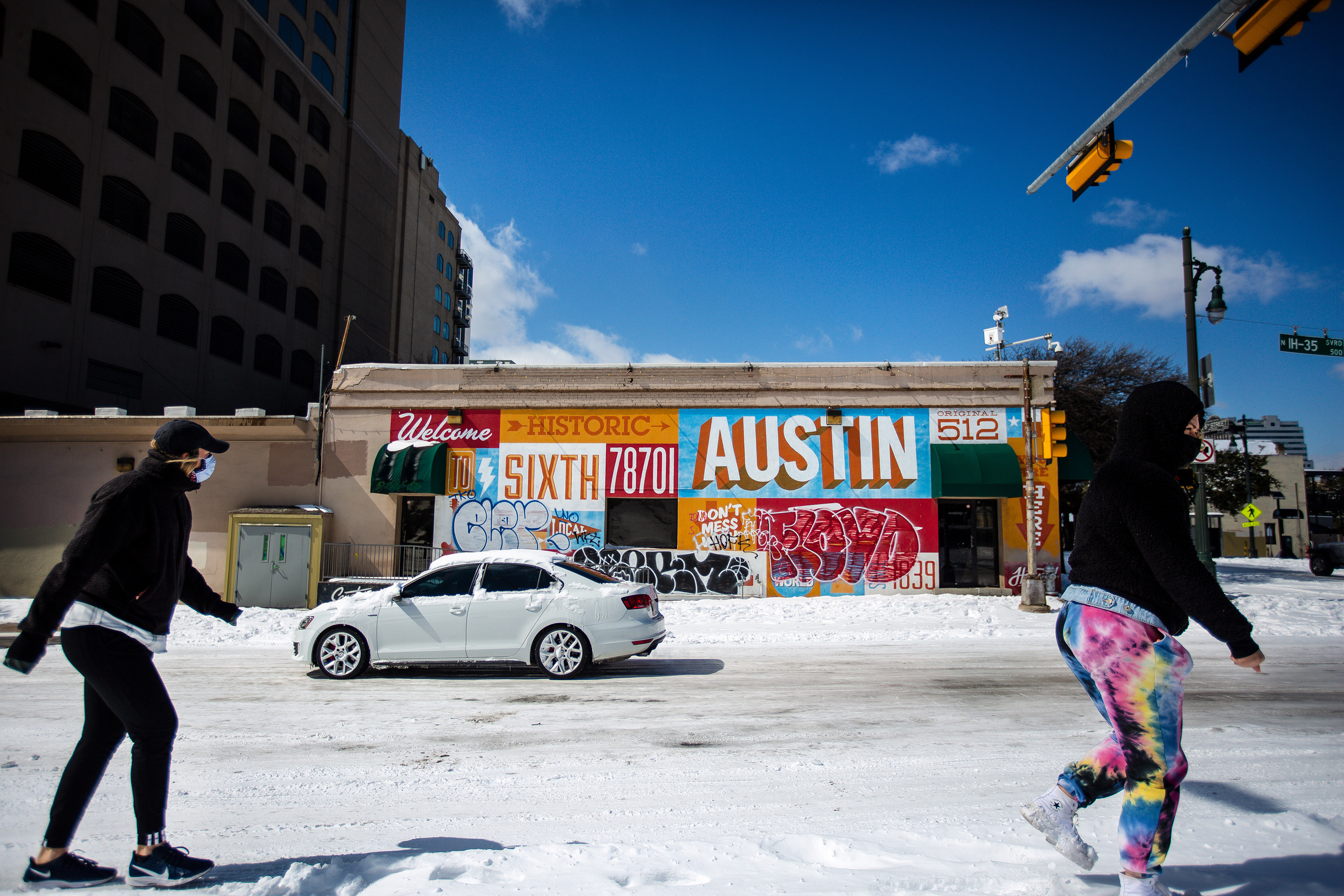 Two people walking past a mural in Austin Texas in the snow