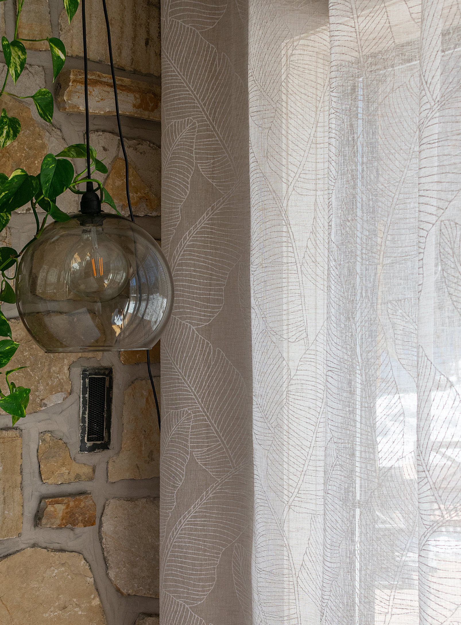 the banana leaf curtains on a window next to a wall and lamp