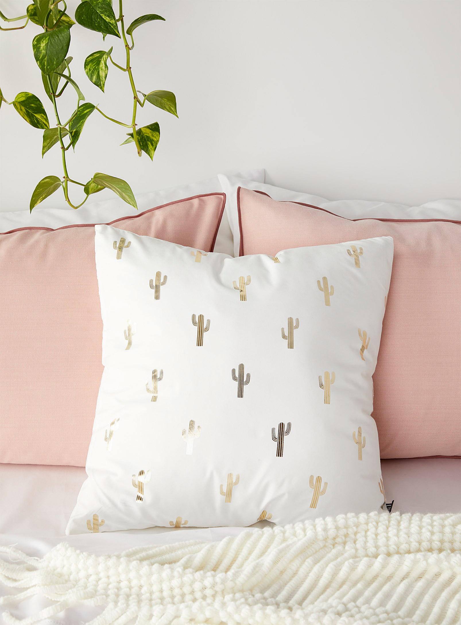 the cactus pillow on a bed as an accent pillow