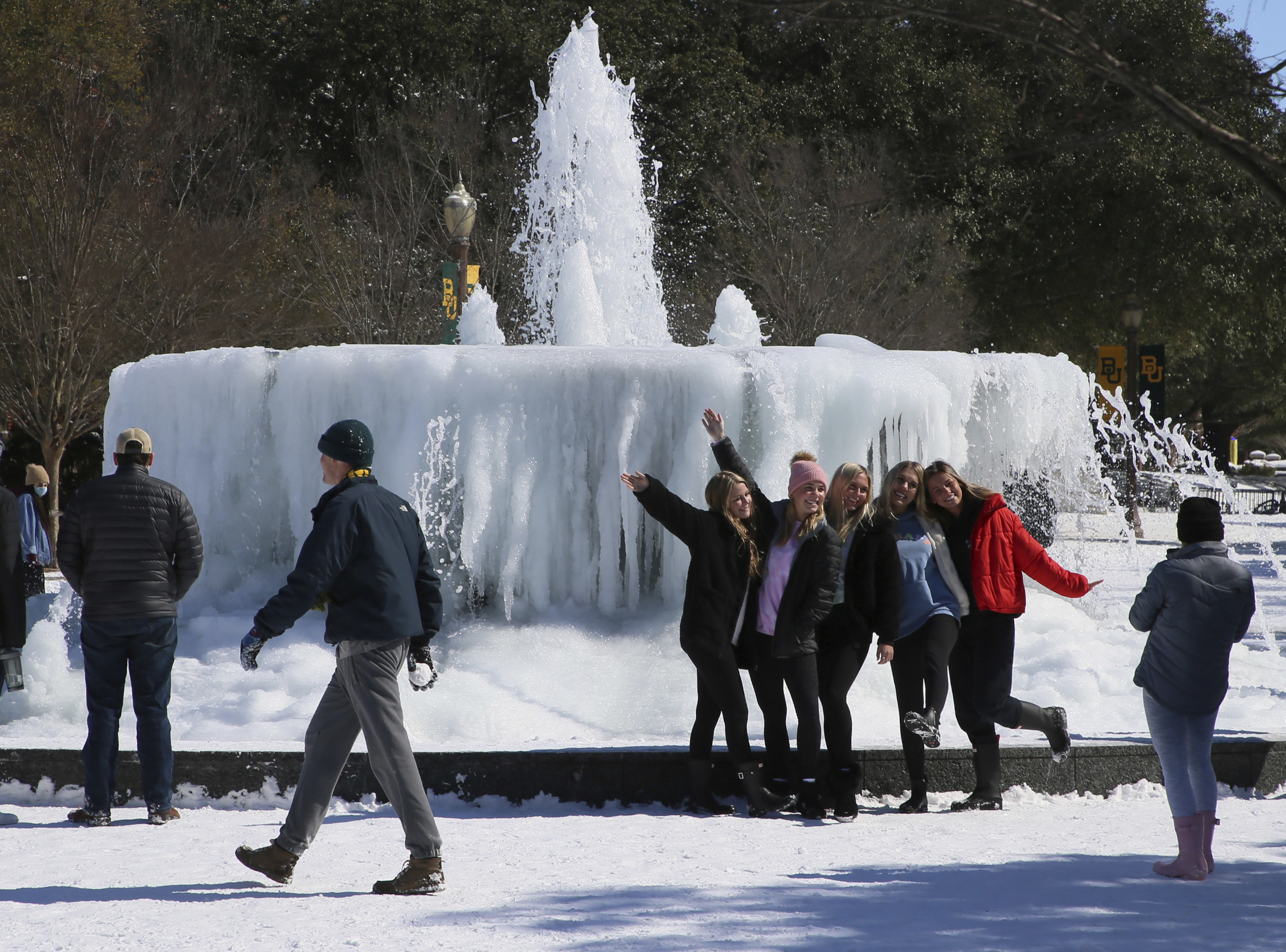 A group of young women posing for a photo together in front of a frozen fountain