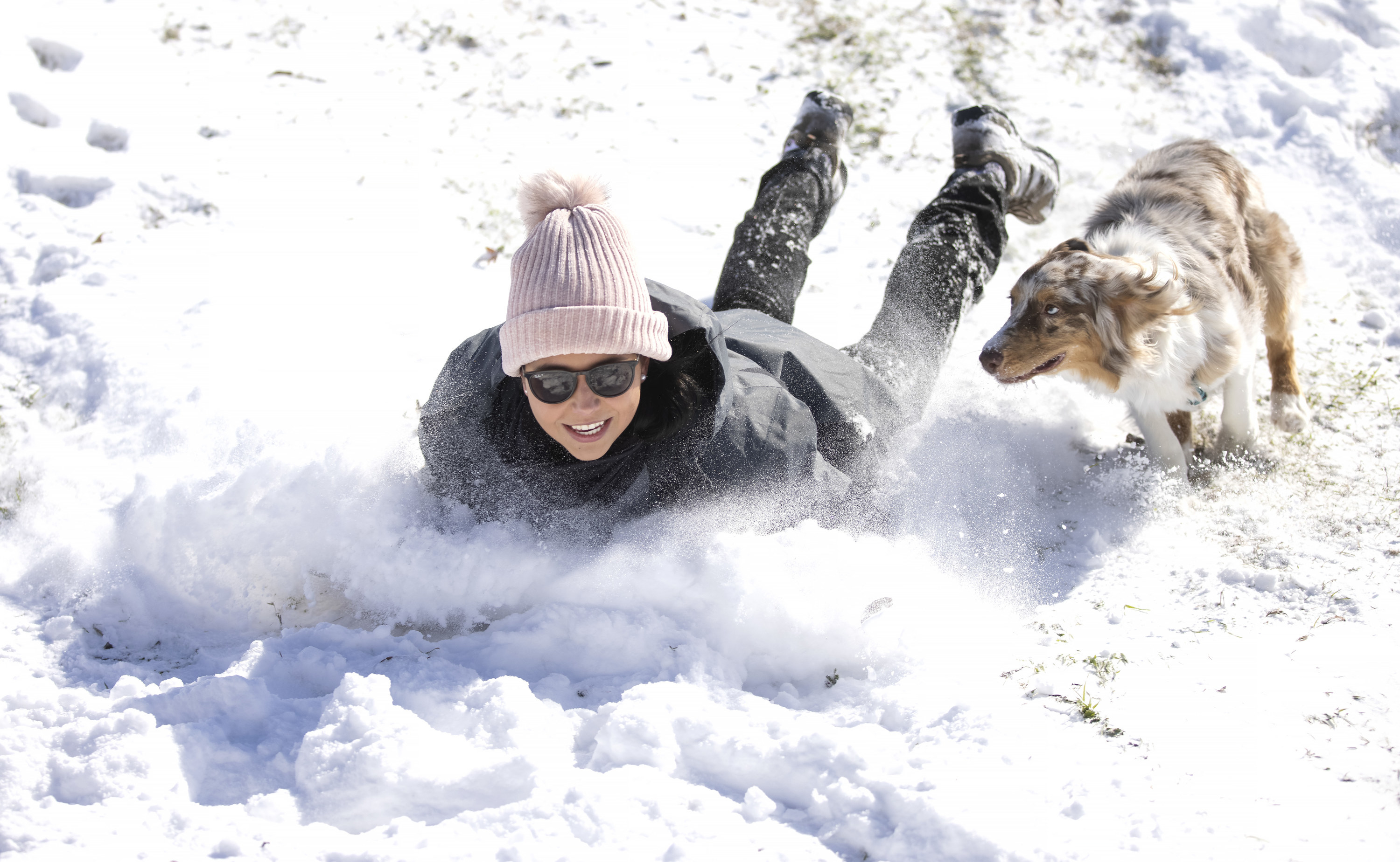A woman sleds down a hill on her stomach chased by her dog