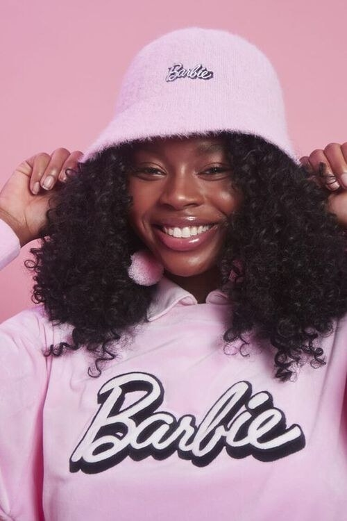 model wearing the hat with the Barbie logo embroidered on the front