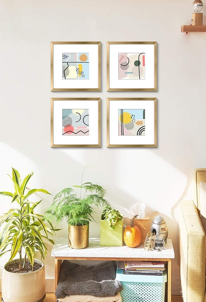 the four frames with the abstract prints inside on the wall