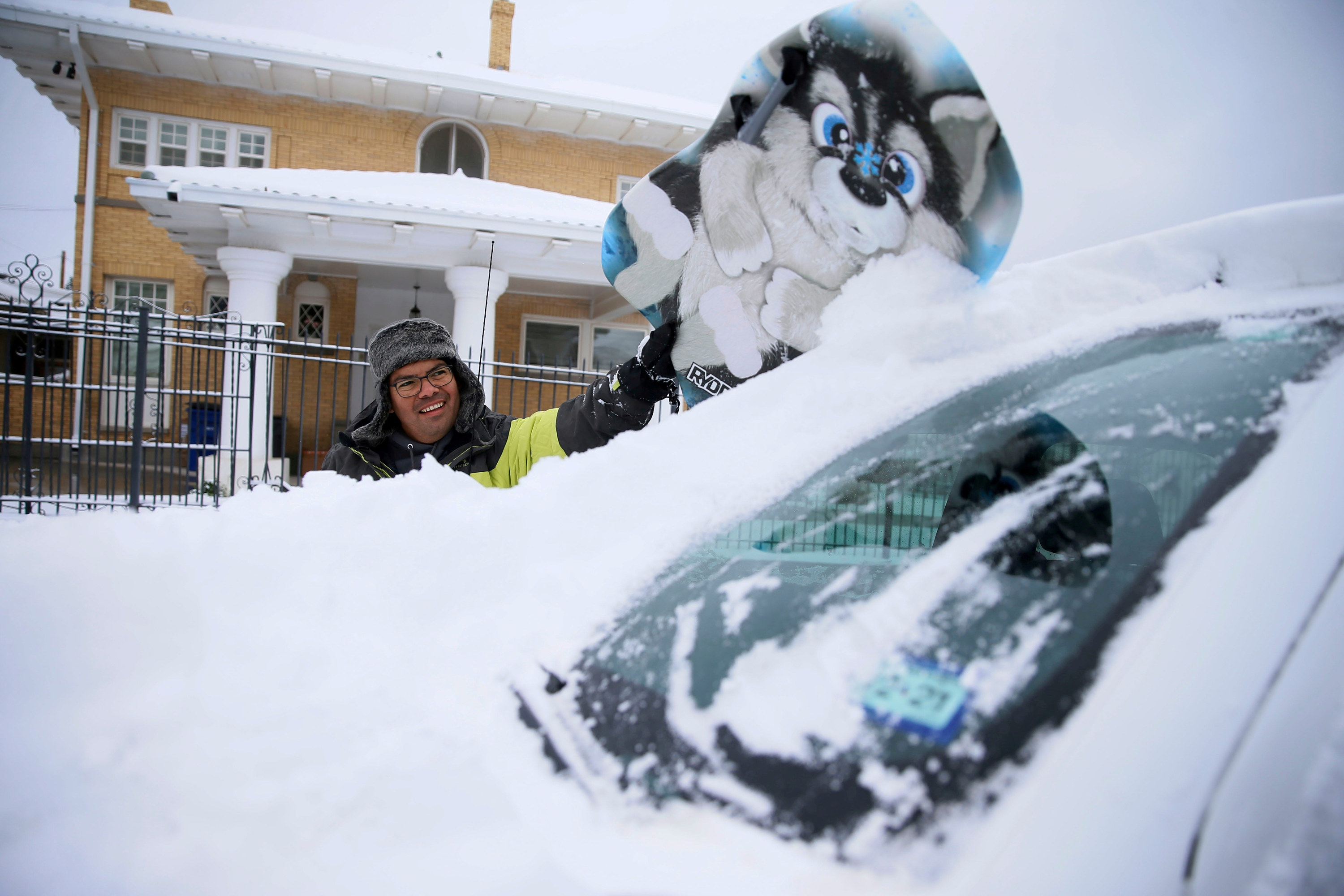 A smiling man cleaning snow off his car